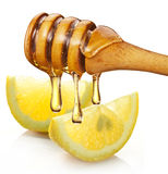 Honey with wood stick pouring onto a slice of lemon. Royalty Free Stock Images