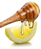 Honey with wood stick pouring onto a slice of lemon. Royalty Free Stock Photography