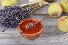 Honey in wooden bowl with honey dipper Stock Photo