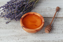 Honey in wooden bowl with honey dipper Stock Images