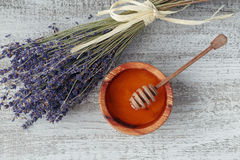 Honey in wooden bowl with honey dipper Stock Photos