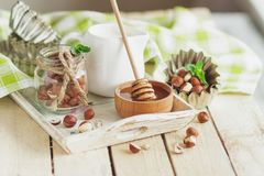 Honey in the wooden bowl, mint leaves, hazelnuts and jar with milk on the wooden tray Royalty Free Stock Images