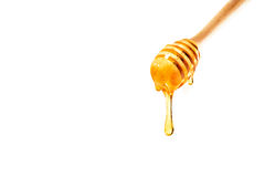 Honey on wooden dipper white background royalty free stock photos