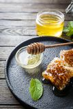 Honey with wooden honey dipper. And honeycomb on dark wood table stock image