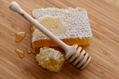 Honey and wooden spoon. Honey in a comb and wooden spoon on wooden background stock images