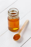 Honey in a wooden spoon and jar Royalty Free Stock Photos