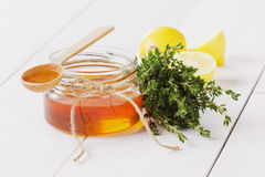 Honey in a wooden spoon and jar Stock Photos