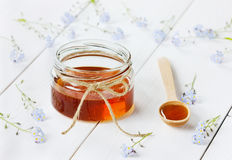 Honey in a wooden spoon and jar Royalty Free Stock Images