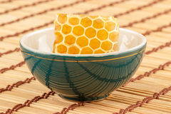 Honeycomb in bowl. Honeycomb in green porcelain bowl on light rustic mat Stock Photos