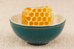 Honeycomb in bowl. Honeycomb in green porcelain bowl on rustic table cloth Stock Images
