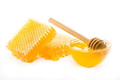 Honeycomb and bowl with honey. And wooden dipper on a white background Royalty Free Stock Images