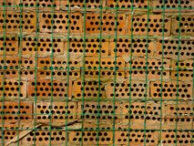 Honeycomb briquet. An orange honeycomb brick wall with a row of green barbed wire in the front Stock Photo