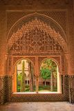 Honeycomb decorated windows of NAsrid Palace , Alhambra, Spain. Honeycomb decorated windows looking onto  patio with trees of NAsrid Palace , Alhambra, Spain Royalty Free Stock Photography