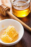 Honeycomb dipper and honey in jar on wooden background Royalty Free Stock Photos