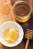 Honeycomb dipper and honey in jar on wooden background Stock Photo