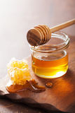 Honeycomb dipper and honey in jar on wooden background Stock Images