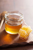 Honeycomb dipper and honey in jar on wooden background Royalty Free Stock Photography