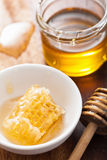 Honeycomb dipper and honey in jar on wooden background Stock Photography