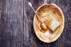 Honeycomb and Dipper. In Wooden Bowl on Wooden Table stock photography