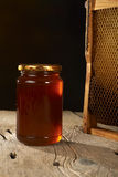 Honeycomb with fresh honey in a vase on wooden table. Stock Image