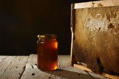 Honeycomb with fresh honey in a vase on wooden table. Royalty Free Stock Image