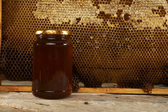Honeycomb with fresh honey in a vase on wooden table. Royalty Free Stock Photography