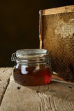 Honeycomb with fresh honey in a vase on wooden table. Stock Photo