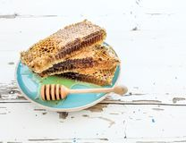 Honeycomb with honey dipper on blue ceramic plate Stock Photo