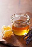Honeycomb and honey in jar on wooden background Stock Photos