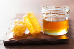 Honeycomb and honey in jar on wooden background Stock Images