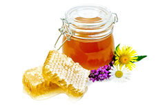 Honeycomb with a jar and flowers Royalty Free Stock Photography