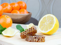 Honeycomb, lemon and mandarins Royalty Free Stock Photography