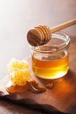 Honeycomb miód w słoju na drewnianym tle i chochla Obrazy Stock