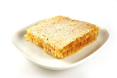 Honeycomb on a plate. Square honeycomb isolated on a white plate Stock Photography