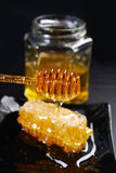Honeycomb with spoon and honey in glass jar Stock Image