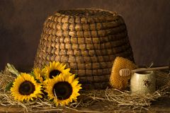 Honeycomb with sunflowers and beehive stock photography