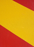 Honeycomb texture. Pattern on an retro-reflecting sign in red and yellow royalty free stock photo