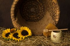 Honeycomb and vintage beehive with sunflowers stock photos