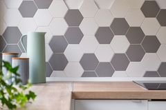 Honeycomb wall tiles and worktop. Kitchen with grey and white honeycomb wall tiles and wooden worktop stock images