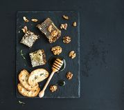 Honeycomb, walnuts, bread slices and honey dipper Stock Photography