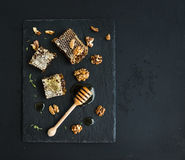Honeycomb, walnuts and honey dipper on black slate Stock Images