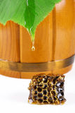 Honeycomb wax, wooden barrel, drop of honey Royalty Free Stock Photos