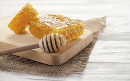 Honeycomb on wooden board and honey dipper on white wooden table stock photo