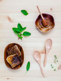 Honeycomb in wooden bowl with herbs mint ,thyme and sage set up. On white wooden background stock photo