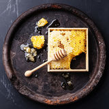 Honeycomb. With wooden honey dipper on black textured background Stock Photos