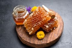 Honeycombs, flowers and jar of honey stock images