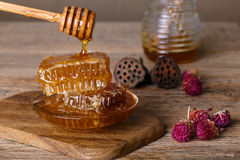 Honeycombs and honey spoon on a wooden board and table Stock Photography
