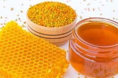 Honeycombs,  jar of dark honey and pollen Stock Photos