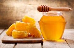 Honeycombs and jar of honey stock photos