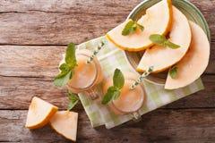 Honeydew melon juice closeup on wooden background, horizontal to Stock Photography